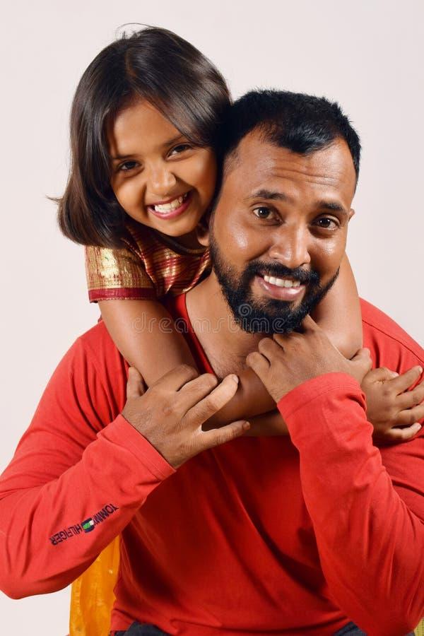 Menina que abraça seu pai e em seus ombros Pune, Maharashtra fotografia de stock royalty free