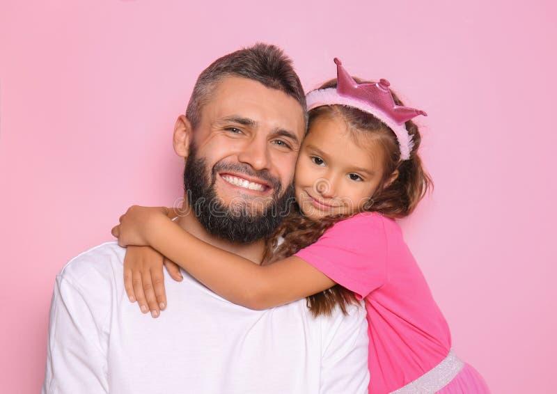Menina que abraça seu pai no fundo da cor imagens de stock