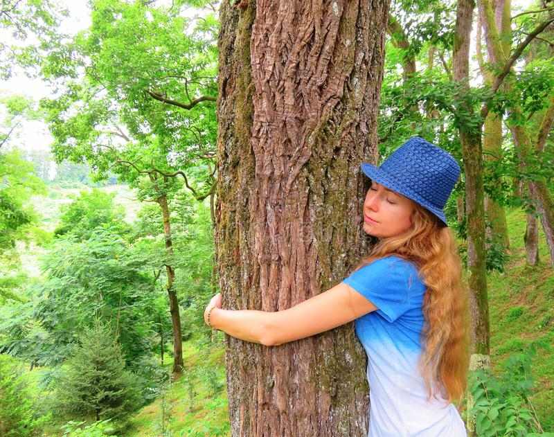 Menina que abraça uma árvore na natureza no verão Menina bonita fotos de stock royalty free