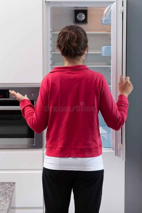 Menina que abre o refrigerador vazio fotografia de stock