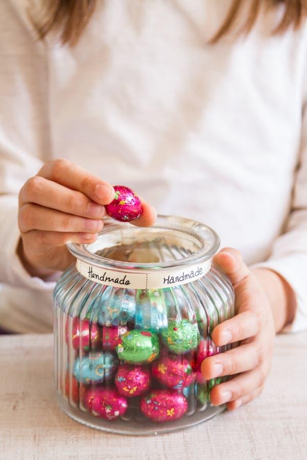 A menina que abre um frasco da folha colorida envolveu doces dos ovos de chocolate imagens de stock