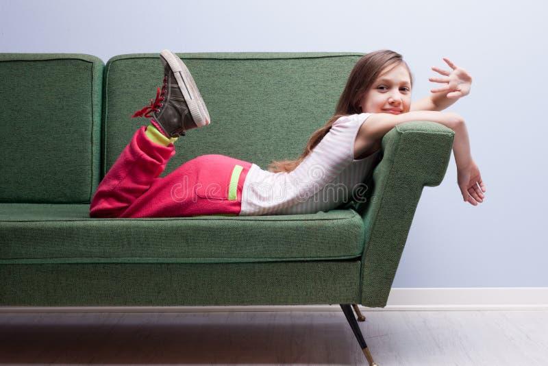 Menina que acena na câmera que encontra-se em um sofá verde fotografia de stock royalty free