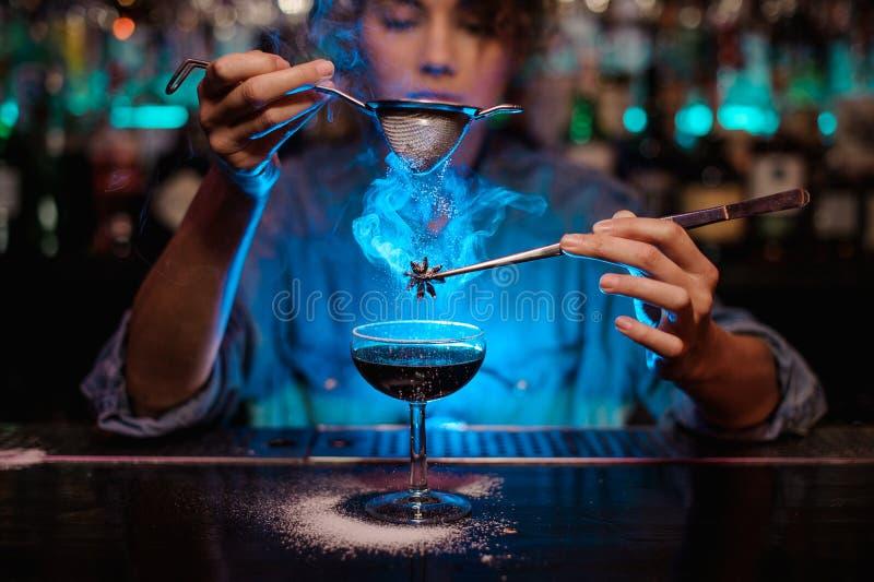 Menina que adiciona a um cocktail marrom e para derramar em um badian ardido na pinça um açúcar pulverizado através do filtro no fotografia de stock