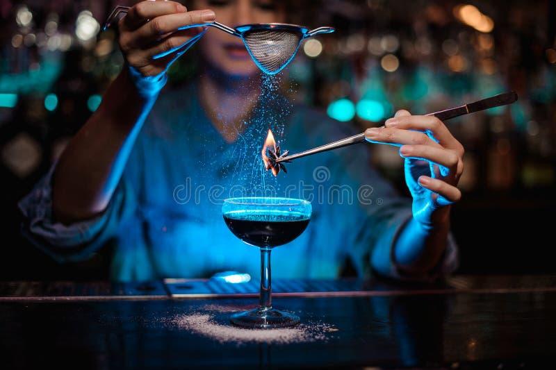 Menina que adiciona a um cocktail marrom e para derramar em um badian ardido na pinça um açúcar pulverizado na luz azul fotografia de stock