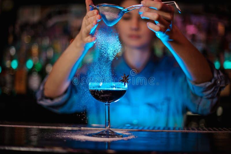 Menina que adiciona a um cocktail marrom um pó do açúcar através do filtro na luz azul imagem de stock