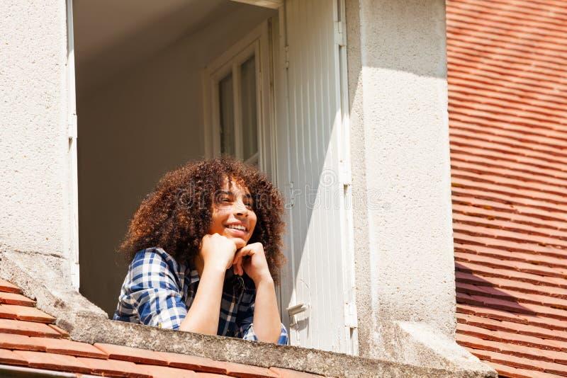 Menina que admira a paisagem da janela do assoalho do sótão imagens de stock