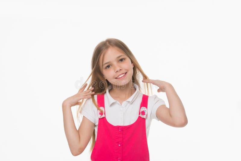 Menina que afaga seu cabelo louro longo Criança bonita com sorriso encantador, beleza e conceito da infância Criança no equipamen fotos de stock royalty free