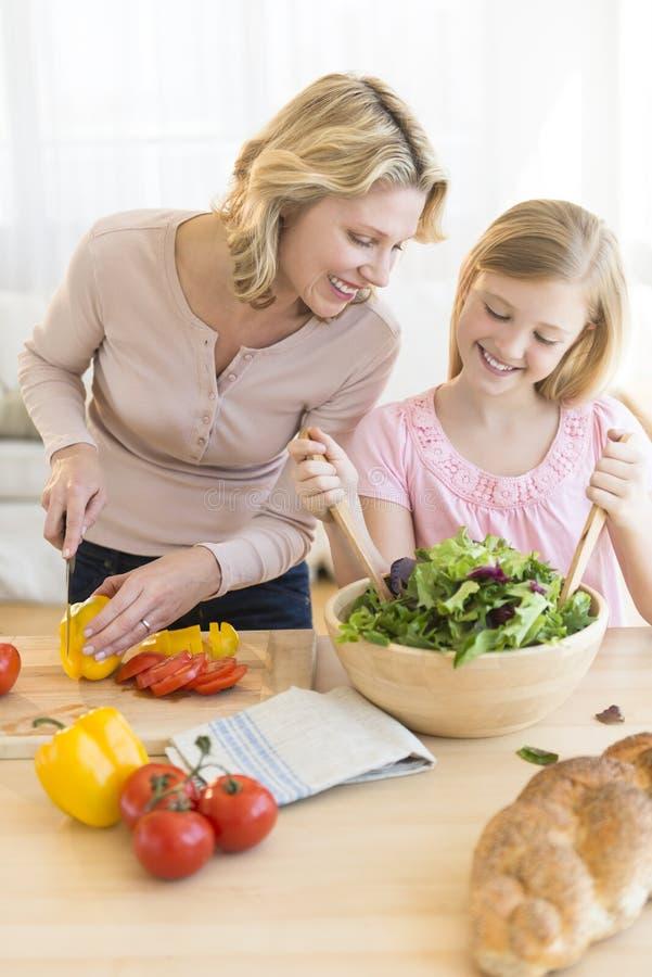 Menina que ajuda à mãe em preparar a salada no contador fotografia de stock