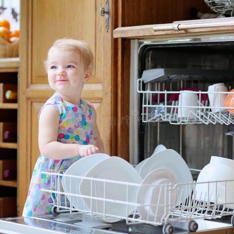 Menina que ajuda com máquina de lavar do prato foto de stock royalty free