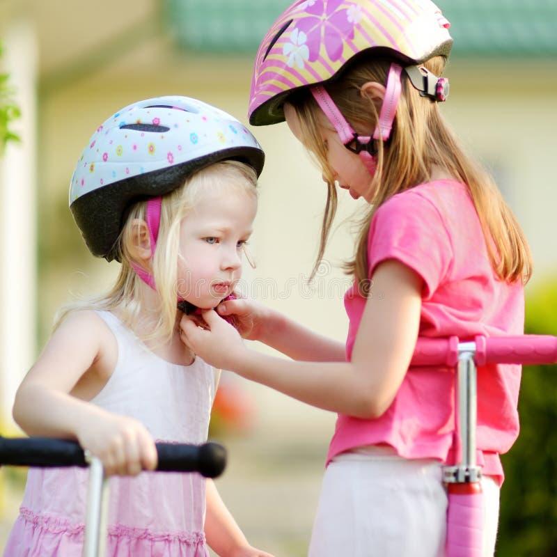 Menina que ajuda sua irmã a pôr sobre um capacete fotos de stock