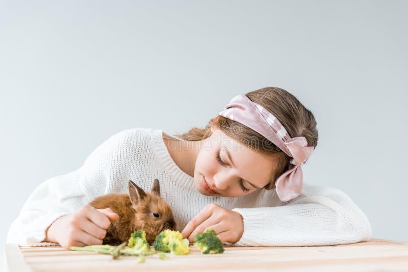 Menina que alimenta o coelho peludo bonito com brócolis na tabela de madeira fotos de stock
