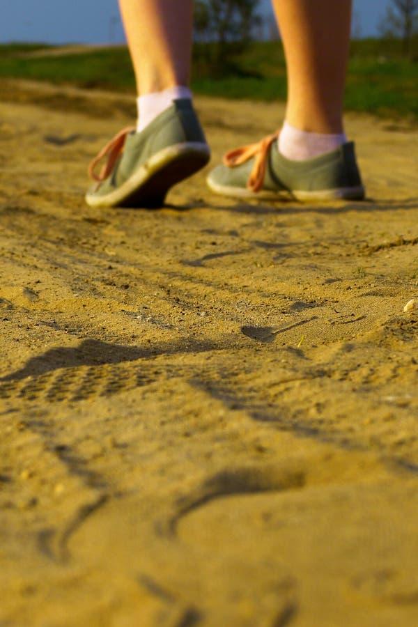 Menina que anda afastado na areia foto de stock royalty free