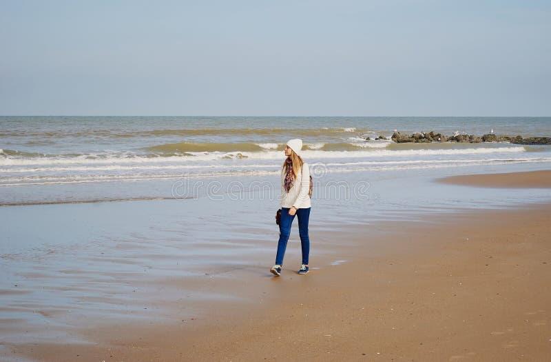 Menina que anda ao longo da costa de mar imagem de stock