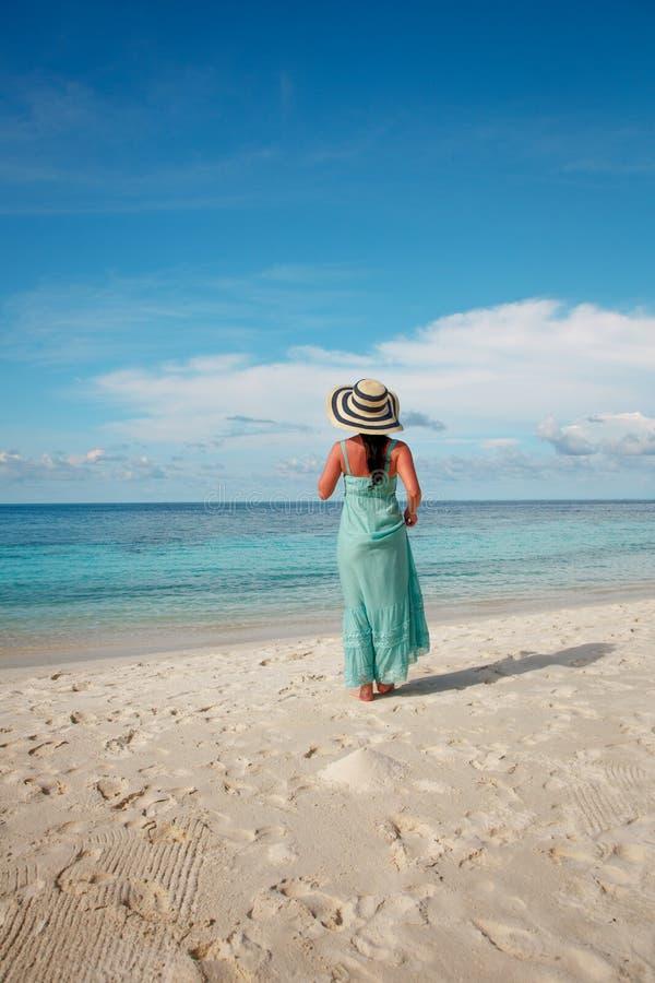 Menina que anda ao longo de uma praia tropical em Maldivas fotografia de stock