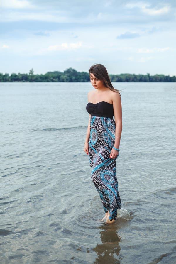 Menina que anda apenas na água e que guarda seu vestido imagem de stock royalty free