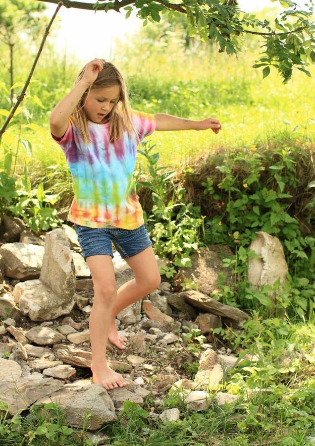 Menina que anda com os pés descalços em rochas imagem de stock royalty free