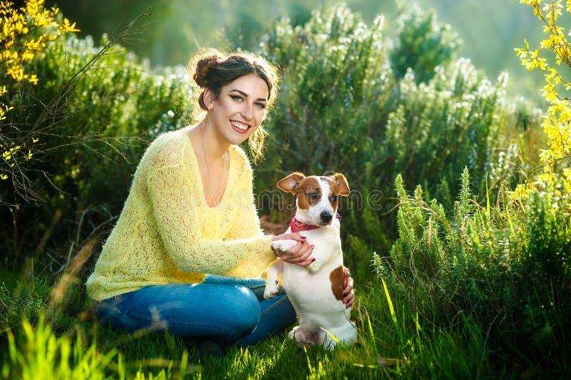 Menina que anda com um cão de caça - Jack Russell Terrier Close-up Mola Copie o espaço imagem de stock royalty free