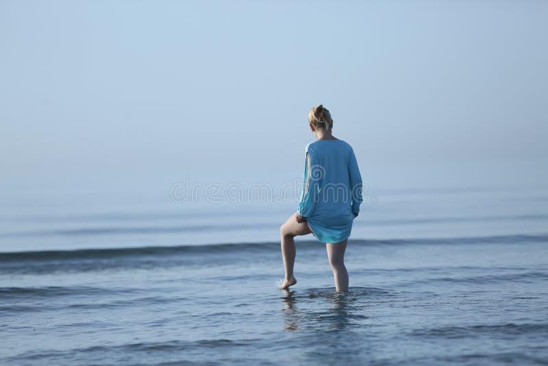 Menina que anda na água imagem de stock