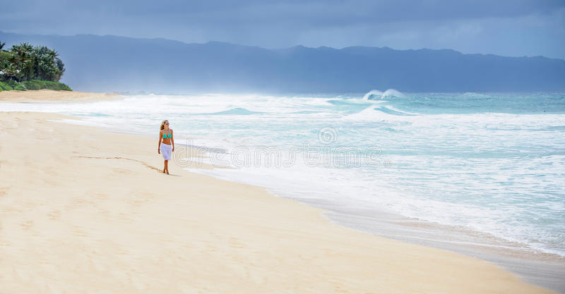 Menina que anda na praia abandonada foto de stock
