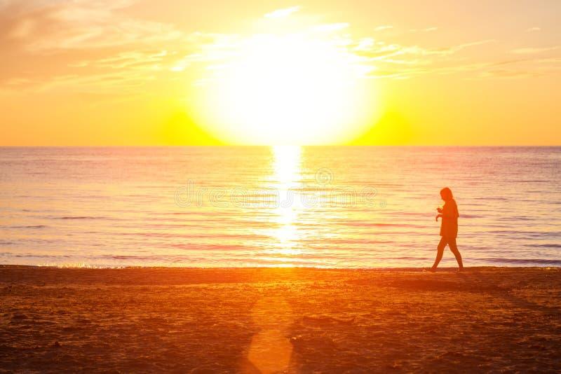 Menina que anda na praia perto do mar no por do sol fotografia de stock