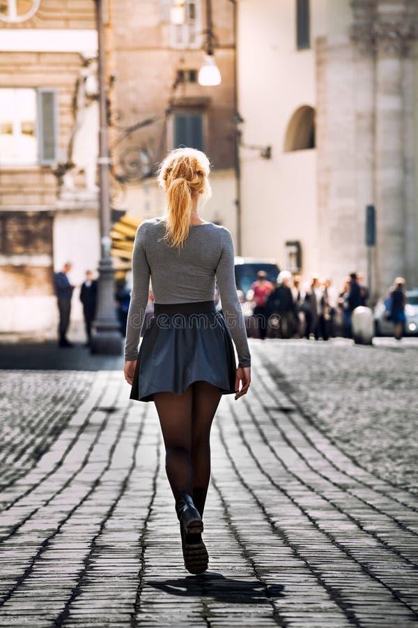 Menina que anda na rua na cidade que veste uma saia back imagem de stock