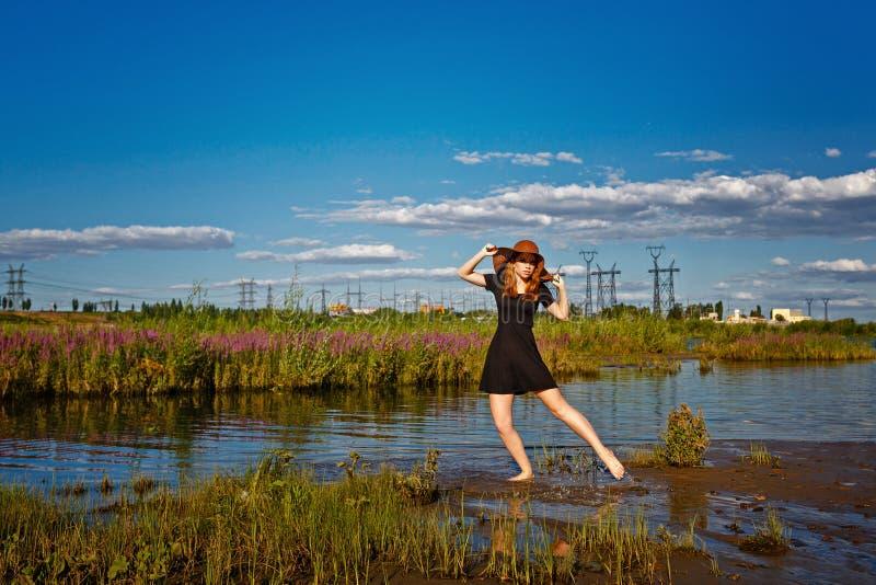 Menina que anda no riverbank imagens de stock