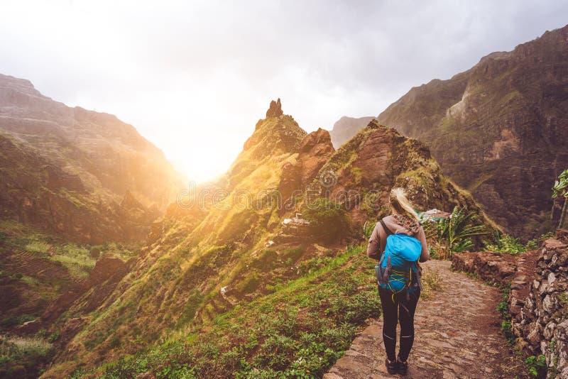 Menina que anda para baixo ao longo da rota trekking ao vale verdejante de Xo-Xo Luz solar morna seable no horizont Ilha de Santo fotos de stock royalty free