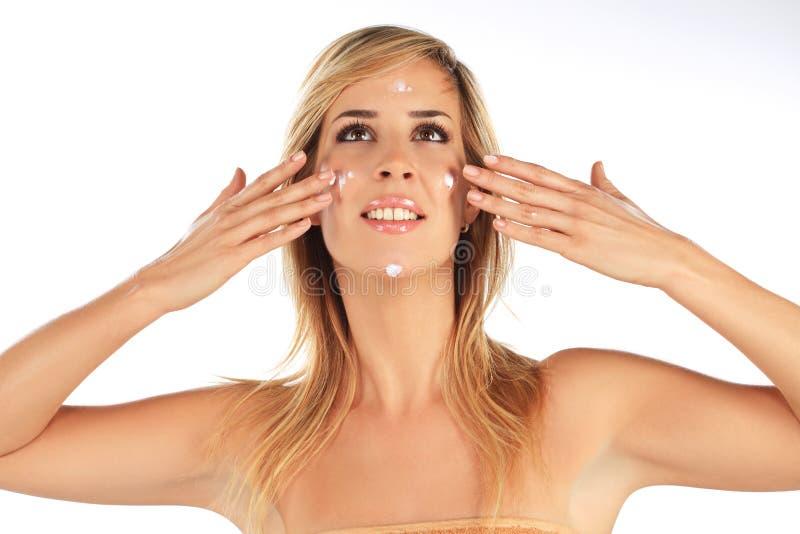 Menina que aplica a nata em sua face imagem de stock