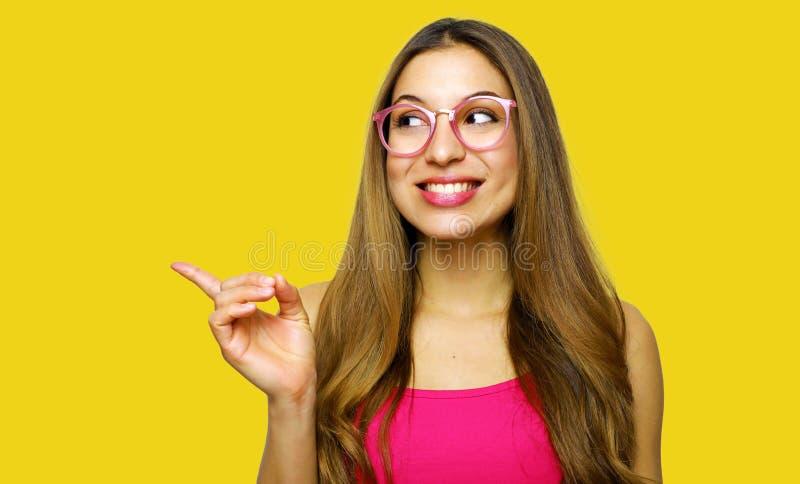 Menina que aponta a exibição no fundo amarelo que olha ao lado Sorriso bonito muito fresco e energético da jovem mulher feliz imagens de stock royalty free
