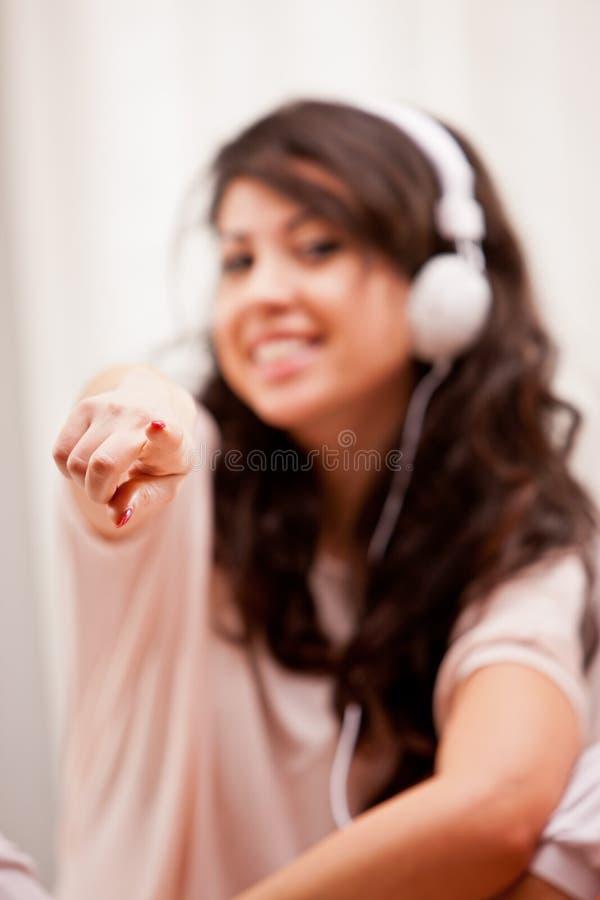 Menina que aponta seu dedo quando música de escuta foto de stock