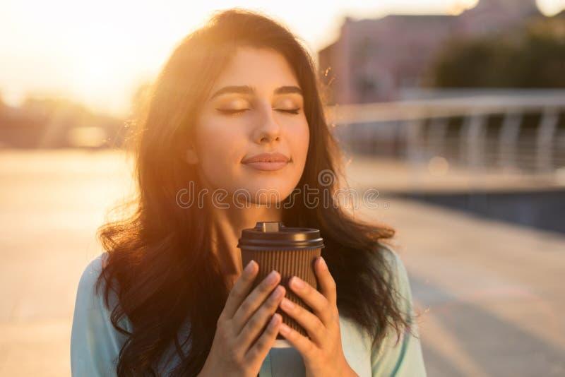 Menina que aprecia o chocolate quente no copo afastado, fora imagem de stock