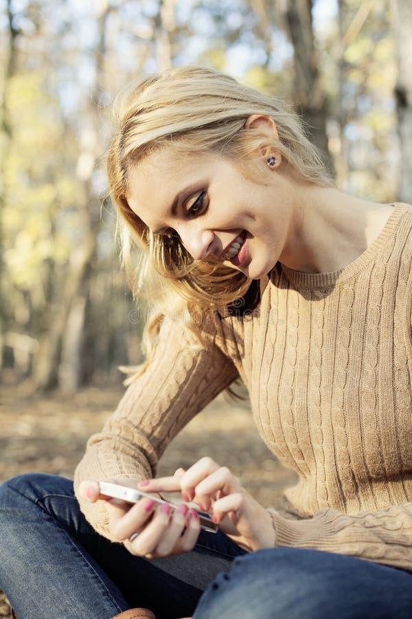 Menina que aprecia o rádio do Internet no smartphone em n foto de stock royalty free
