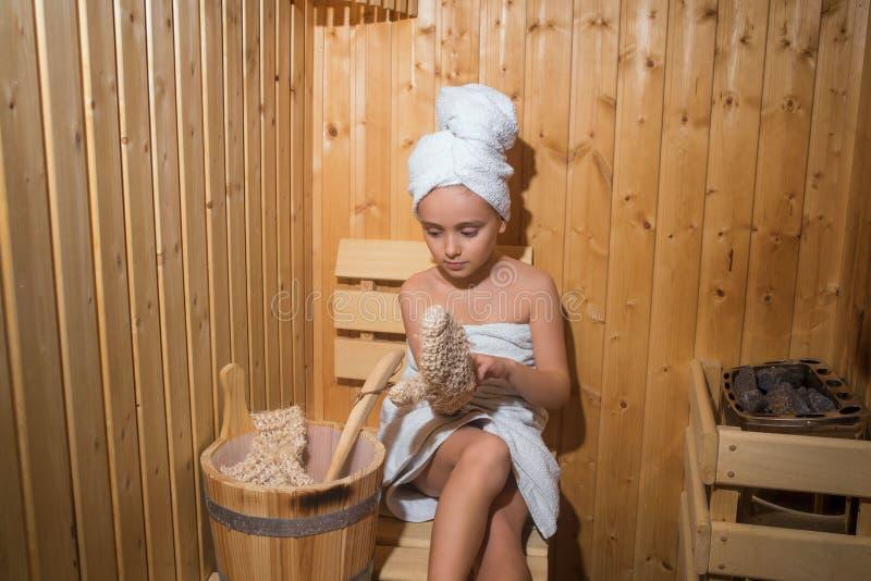 Menina que aprecia uma estada de relaxamento na sauna Moça que relaxa na sauna, menina em um tratamento dos termas em uma sauna t foto de stock royalty free