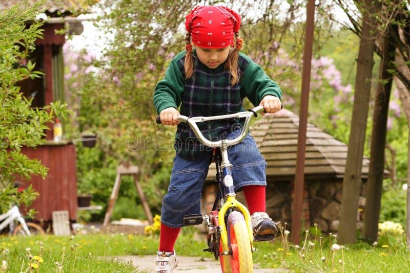 Menina que aprende a bicicleta da movimentação fotos de stock royalty free