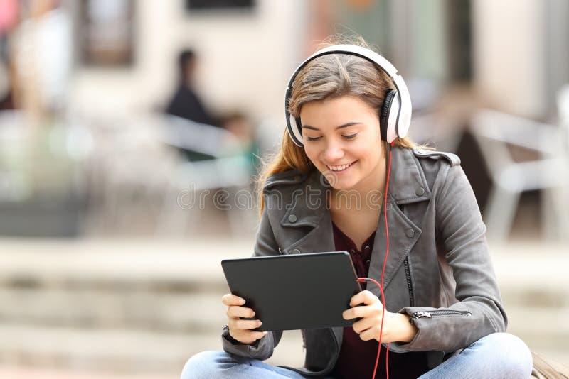 Menina que aprende na linha com uma tabuleta e os fones de ouvido foto de stock royalty free