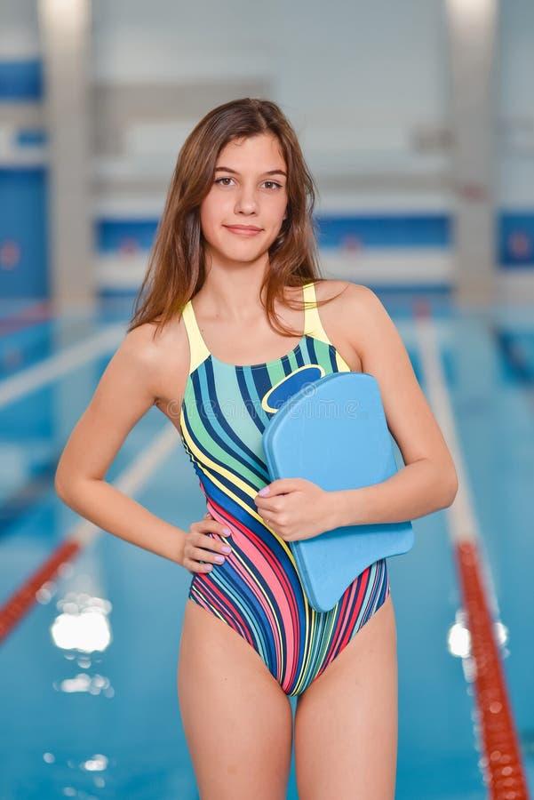 Menina que aprende nadar com placa na piscina fotografia de stock royalty free