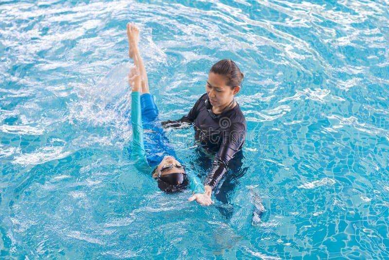 Menina que aprende nadar com treinador fotografia de stock royalty free