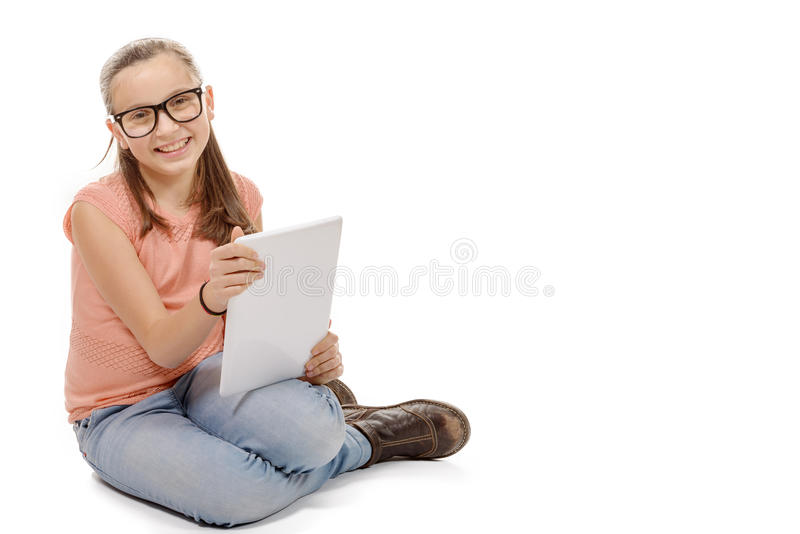 Menina que assenta o assoalho com um tablet pc imagem de stock royalty free