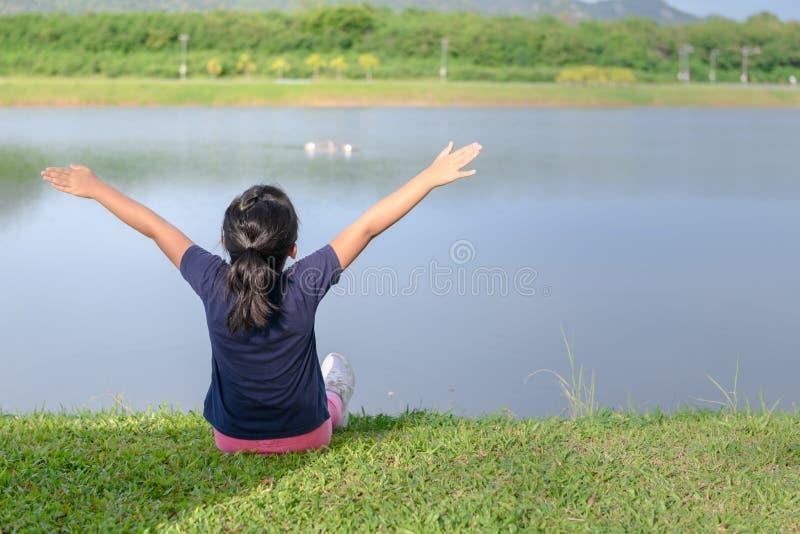 A menina que aumenta os braços aproxima o lago fotografia de stock