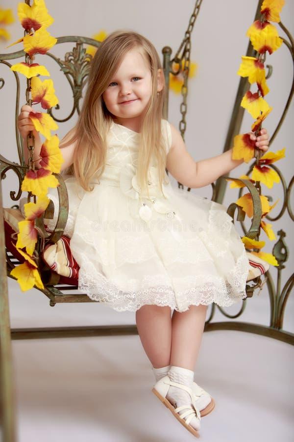 Menina que balanç em um balanço foto de stock royalty free