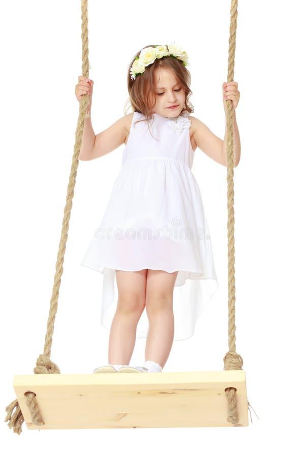 Menina que balança em um balanço imagem de stock