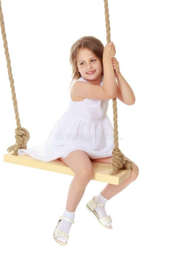 Menina que balança em um balanço foto de stock