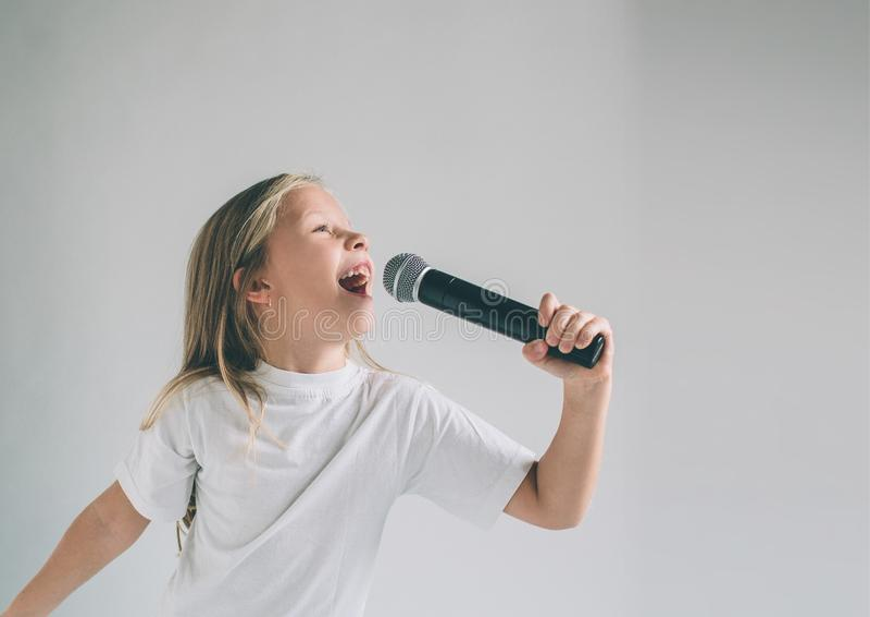 Menina que balança para fora Imagem de uma criança que canta ao microfone, isolada na luz Retrato emocional de uma criança atrati imagem de stock