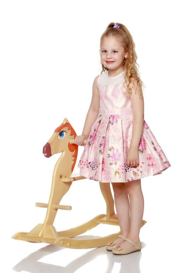 Menina que balan?a em um cavalo de madeira fotografia de stock royalty free