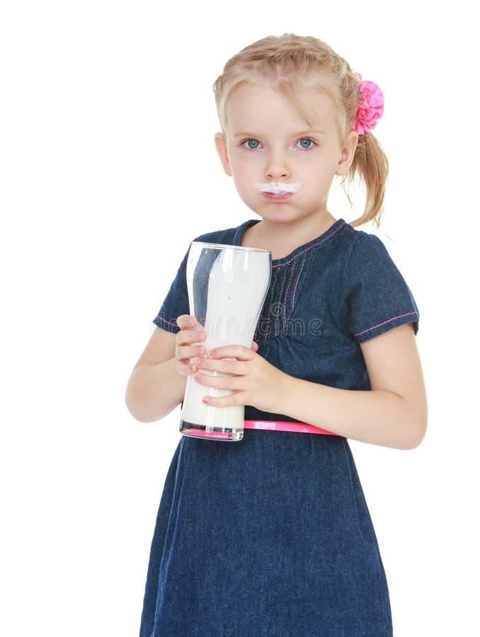 Menina que bebe de um grande vidro do leite fotos de stock royalty free