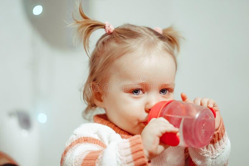 Menina que bebe de uma garrafa fotos de stock