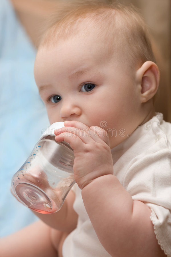 Menina que bebe do frasco plástico fotografia de stock