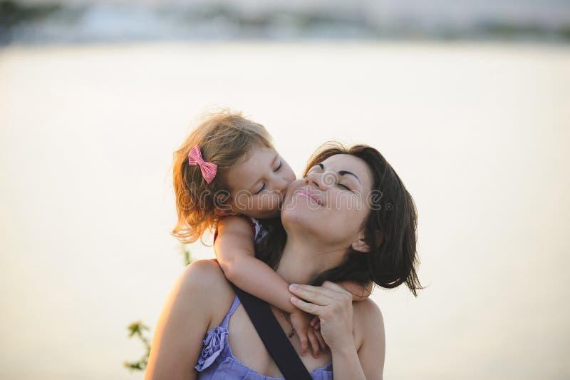 Menina que beija a mãe foto de stock royalty free