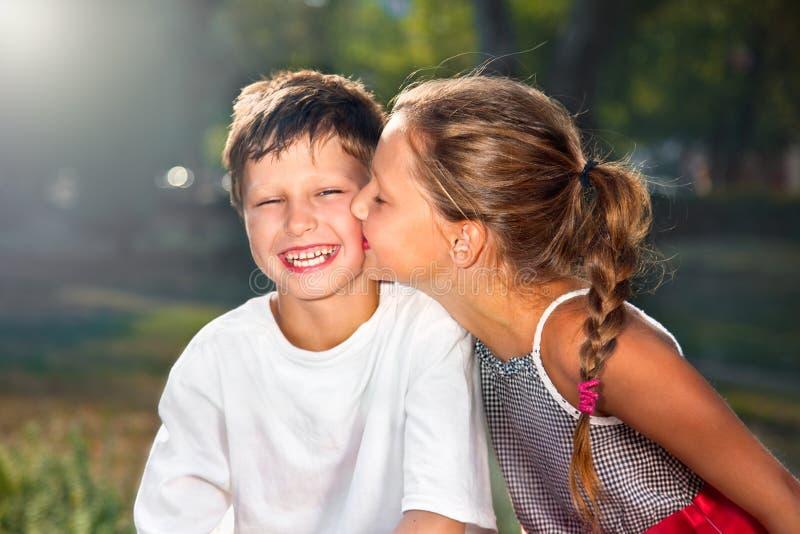 Menina que beija o menino imagem de stock