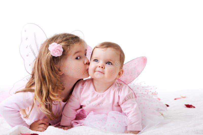 Menina que beija sua irmã do bebê imagem de stock royalty free
